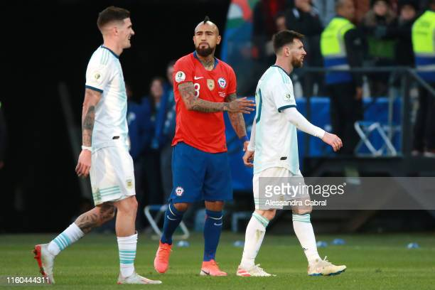 Lionel Messi of Argentina walks past Arturo Vidal of Chile as he leaves the pitch after being sent off during the Copa America Brazil 2019 Third...