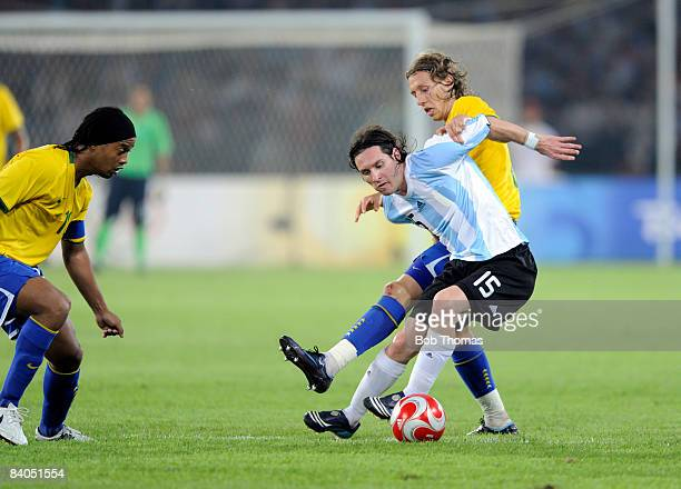 Lionel Messi of Argentina with Lucas and Ronaldinho of Brazil during the men's football semifinal match between Argentina and Brazil at Workers'...