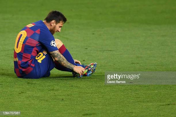 Lionel Messi of Barcelona adjusts his boots during the UEFA Champions League round of 16 second leg match between FC Barcelona and SSC Napoli at Camp...