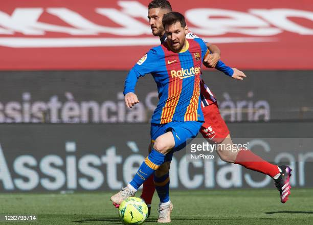 Lionel Messi of Barcelona and Koke Resurreccion of Atletico Madrid compete for the ball during the La Liga Santander match between FC Barcelona and...