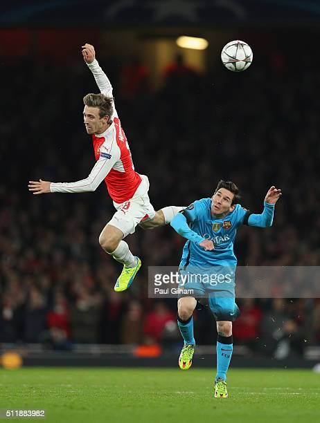 Lionel Messi of Barcelona and Nacho Monreal of Arsenal battle for posession during the UEFA Champions League round of 16 first leg match between...
