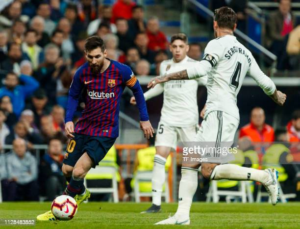 Lionel Messi of Barcelona and Sergio Ramos of Real Madrid battle for the ball during the La Liga match between Real Madrid CF and FC Barcelona at...
