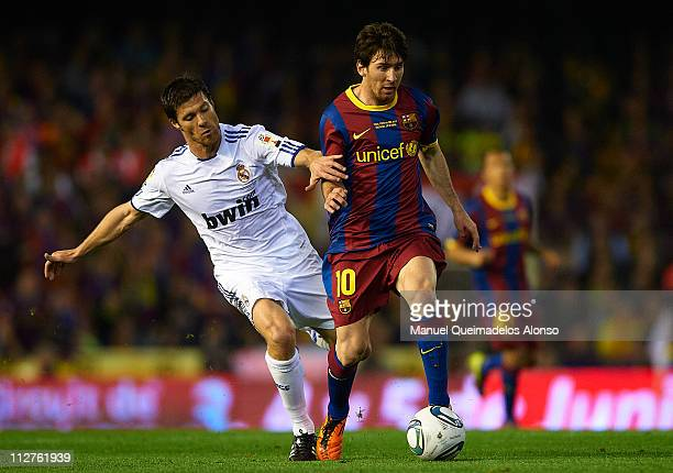 Lionel Messi of Barcelona and Xabi Alonso of Real Madrid compete for the ball during the Copa del Rey final match between Real Madrid and Barcelona...