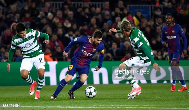 Lionel Messi of Barcelona attempts to get past Marcos Acuna of Sporting Lisbon and Fabio Coentrao of Sporting Lisbon during the UEFA Champions League...