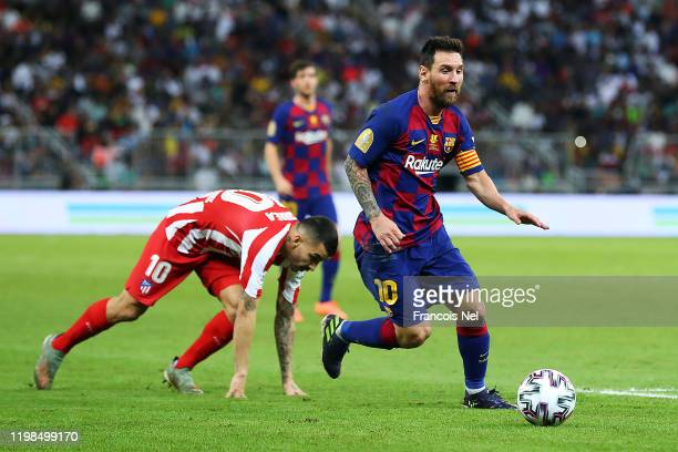 Lionel Messi of Barcelona avoids Angel Correa of Athletico Madrid during the Supercopa de Espana SemiFinal match between FC Barcelona and Club...