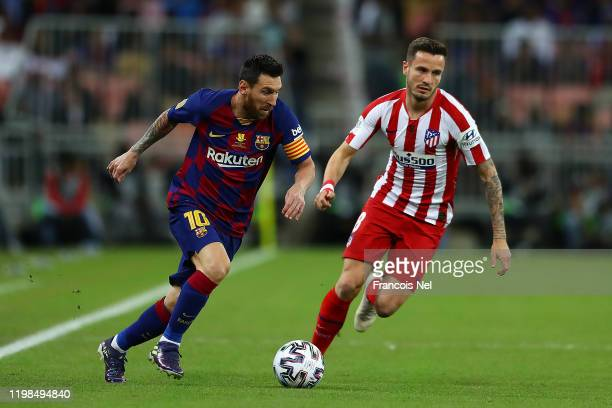 Lionel Messi of Barcelona avoids Saul Niguez of Athletico Madrid during the Supercopa de Espana SemiFinal match between FC Barcelona and Club...