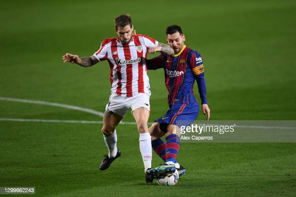 Lionel Messi of Barcelona battles for possession with Inigo Martinez of Athletic Bilbao during the La Liga Santander match between FC Barcelona and...