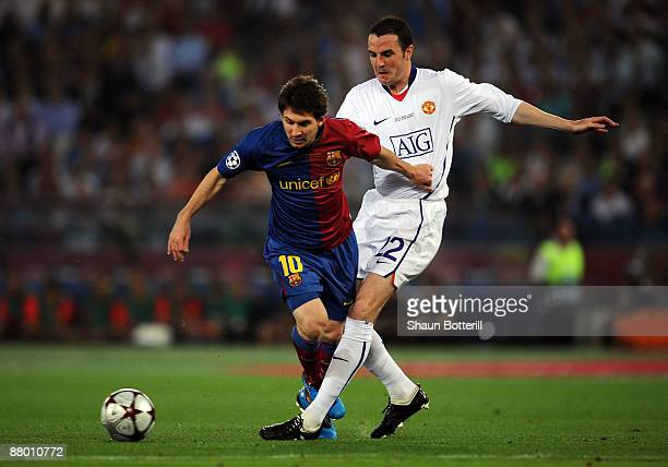 Lionel Messi of Barcelona battles for the ball John O'Shea of Manchester United during the UEFA Champions League Final match between Barcelona and...