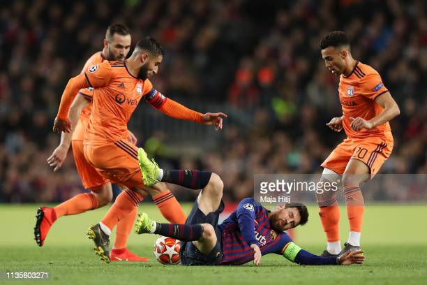 Lionel Messi of Barcelona battles with Nabil Fekir and Fernando Marcal of Olympique Lyonnais during the UEFA Champions League Round of 16 Second Leg...