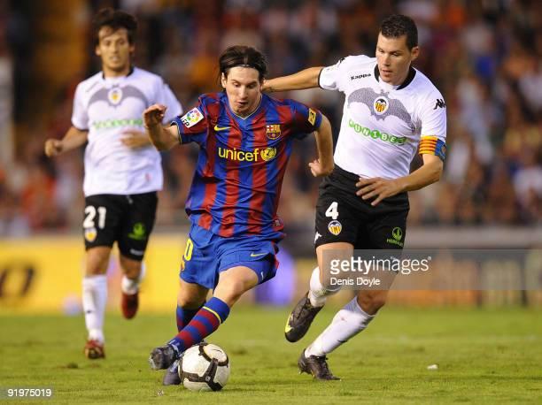 Lionel Messi of Barcelona beats David Navarro of Valencia during the La Liga Match between Valencia and Barcelona at Estadio Mestalla on October 17,...