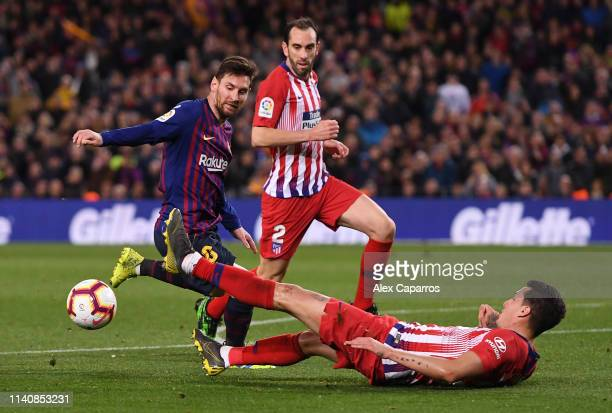Lionel Messi of Barcelona beats Jose Gimenez and of Atletico Madrid as he scores his team's second goal during the La Liga match between FC Barcelona...