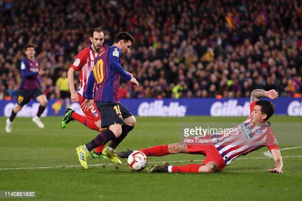 Lionel Messi of Barcelona beats Jose Gimenez of Atletico Madrid as he scores his team's second goal during the La Liga match between FC Barcelona and...