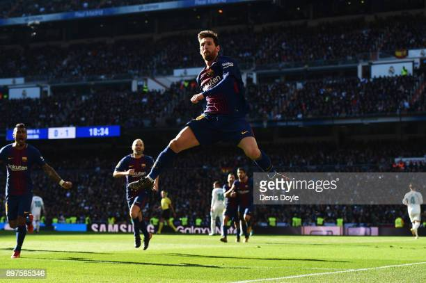 Lionel Messi of Barcelona celebrates after scoring his sides second goal during the La Liga match between Real Madrid and Barcelona at Estadio...