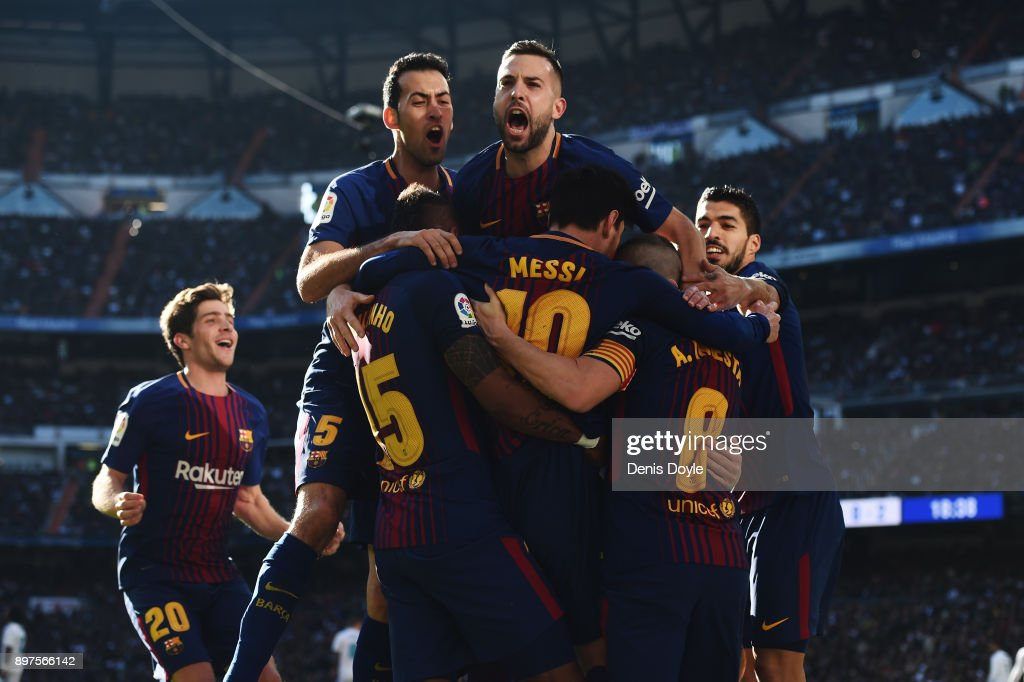 Lionel Messi of Barcelona celebrates after scoring his sides second goal with his team mates during the La Liga match between Real Madrid and Barcelona at Estadio Santiago Bernabeu on December 23, 2017 in Madrid, Spain.
