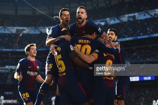 Lionel Messi of Barcelona celebrates after scoring his sides second goal with his team mates during the La Liga match between Real Madrid and...