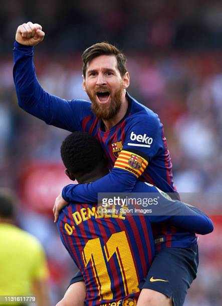 Lionel Messi of Barcelona celebrates after scoring his team's second goal with his teammate Ousmane Dembele during the La Liga match between Sevilla...
