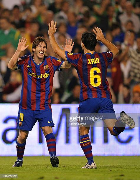 Lionel Messi of Barcelona celebrates after scoring the 20 goal with teammate Xavi Hernandez during the La Liga match between Racing Santander and...