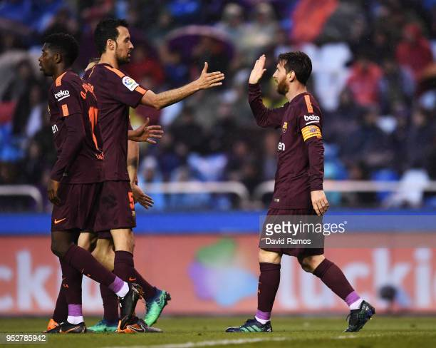 Lionel Messi of Barcelona celebrates as he scores his sides second goal with Sergio Busquets of Barcelona during the La Liga match between Deportivo...