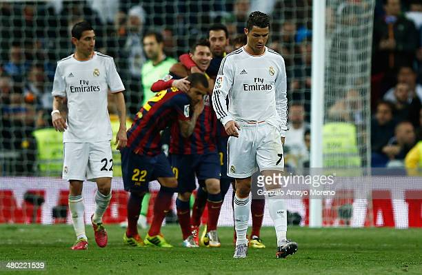 Lionel Messi of Barcelona celebrates scoring his team's third goal with team mates as Cristiano Ronaldo of Real Madrid look dejected during the La...