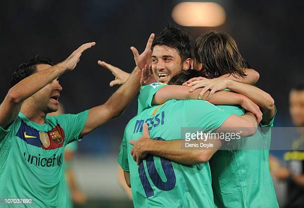 Lionel Messi of Barcelona celebrates with David Villa and Xavi Hernandez after scoring Barcelona's opening goal during the La Liga match between UD...