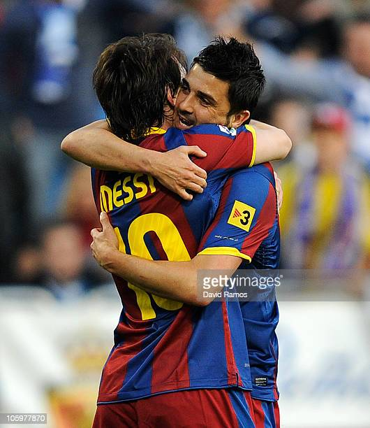 Lionel Messi of Barcelona celebrates with his teammate David Villa after scoring his side first goal during the La Liga match between Real Zaragoza...