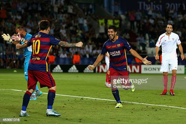 Lionel Messi of Barcelona celebrates with Luis Suarez of Barcelona after Rafinha of Barcelona scored their third goal during the UEFA Super Cup...