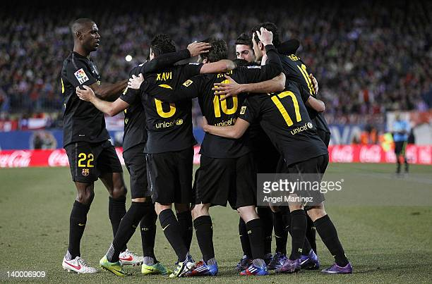 Lionel Messi of Barcelona celebrates with team mates after scoring their side second goal during the La Liga match between Atletico Madrid and...