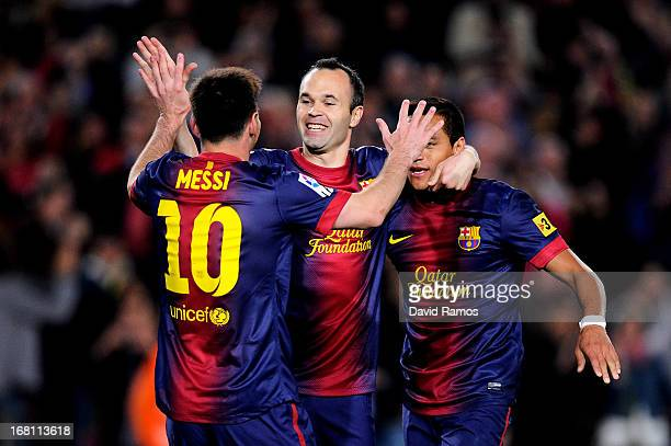 Lionel Messi of Barcelona celebrates with teammates Andres Iniesta and Alexis Sanchez after scoring his team's fourth goal during the La Liga match...