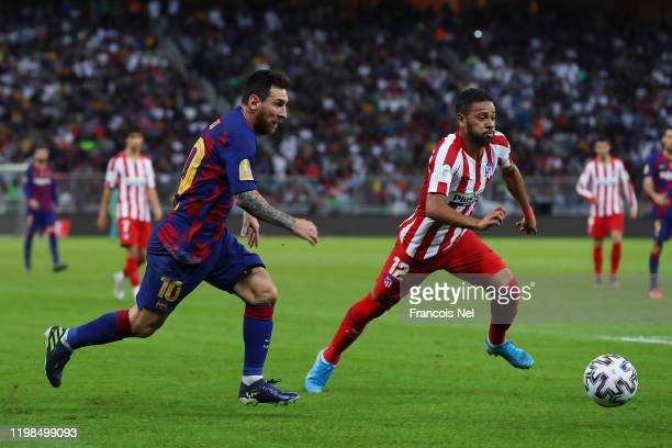 Lionel Messi of Barcelona challenges Renan Lodi of Athletico Madrid during the Supercopa de Espana SemiFinal match between FC Barcelona and Club...
