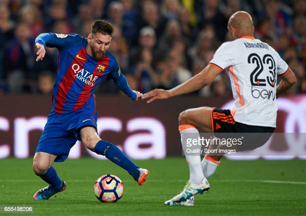 Lionel Messi of Barcelona competes for the ball with Aymen Abdennour of Valencia during the La Liga match between FC Barcelona and Valencia CF at...