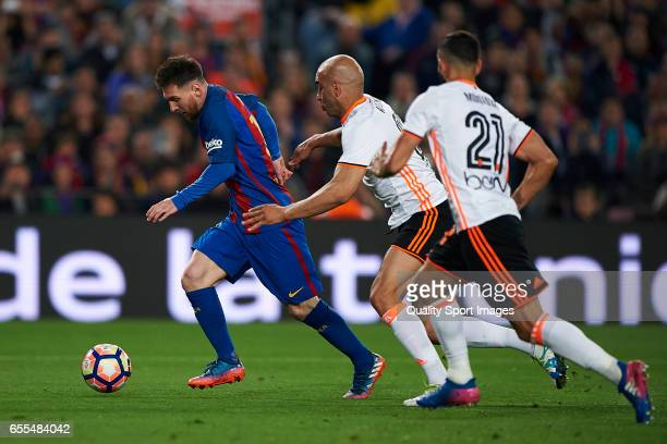 Lionel Messi of Barcelona competes for the ball with Martin Montoya and Aymen Abdennour of Valencia during the La Liga match between FC Barcelona and...