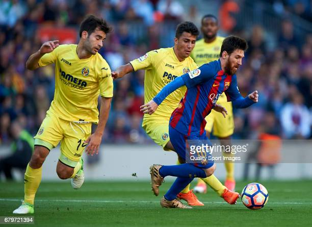 Lionel Messi of Barcelona competes for the ball with Rodrigo Hernandez and Manuel Trigueros of Villarreal during the La Liga match between FC...