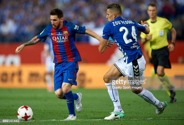 Lionel Messi of Barcelona competes for the ball with Zouhair Feddal of Deportivo Alaves during the Copa Del Rey Final match between FC Barcelona and...