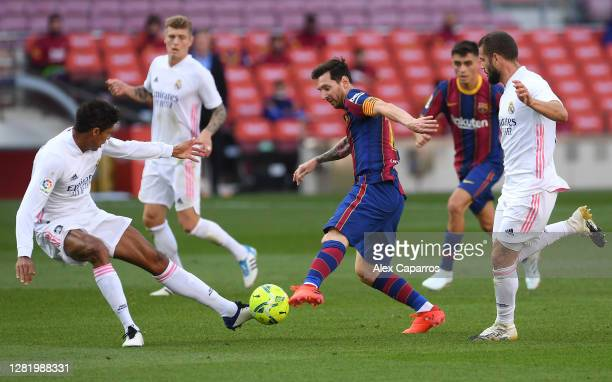 Lionel Messi of Barcelona controls the ball as Raphael Varane of Real Madrid and Luka Modric of Real Madrid look on during the La Liga Santander...