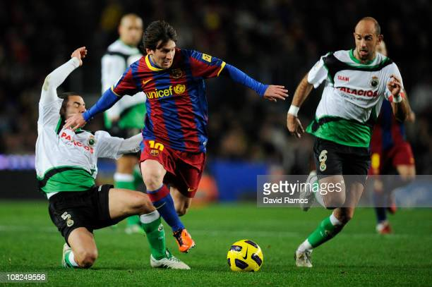 Lionel Messi of Barcelona duels for the ball against Mehdi Lacen and Domingo Cisma of Racing Santander during the La Liga match between Barcelona and...