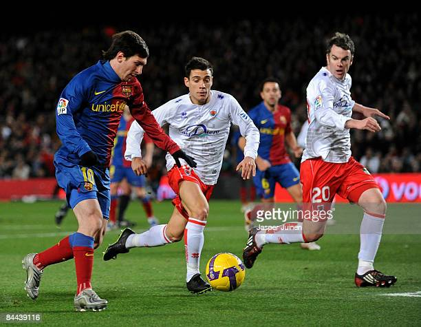 Lionel Messi of Barcelona duels for the ball with Carlos Bellvis and Sergio Boris of Numancia during the La Liga match between Barcelona and Numancia...