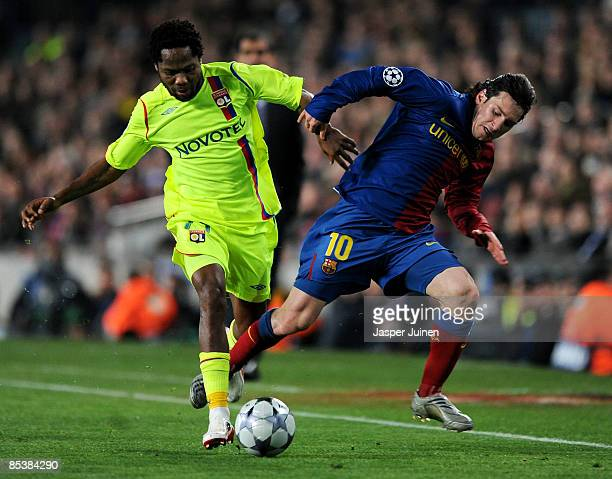 Lionel Messi of Barcelona duels for the ball with Jean II Makoun of Lyon during the UEFA Champions League First knockout round second leg match...