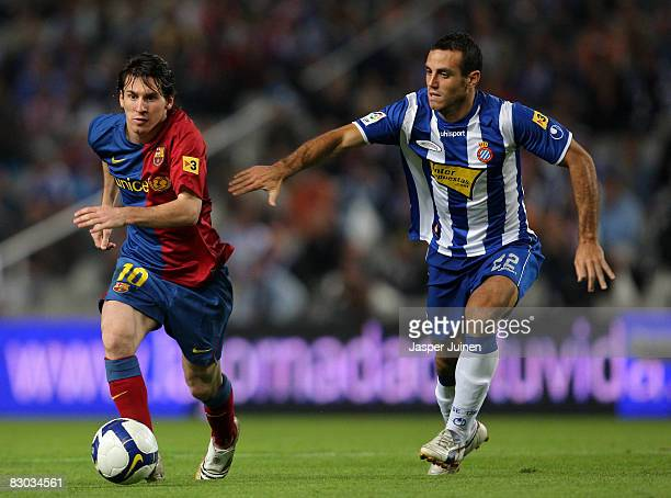 Lionel Messi of Barcelona duels for the ball with Moises Perez of Espanyol during the La Liga match between Espanyol and Barcelona at the Montjuic...