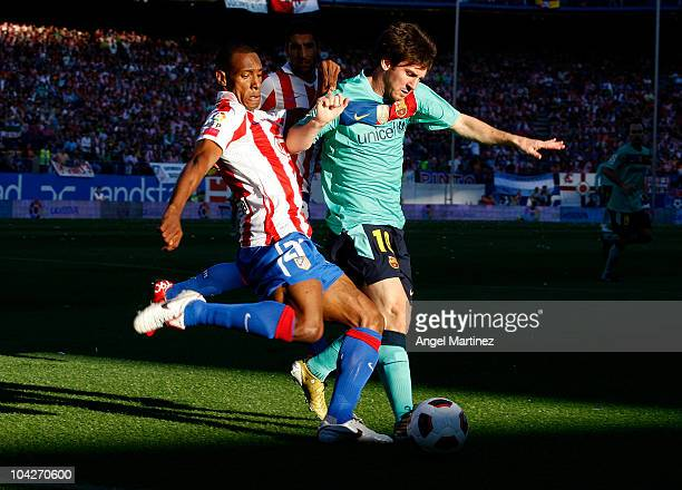 Lionel Messi of Barcelona fights for the ball with Luis Amaranto Perea of Atletico Madrid during the La Liga match between Atletico Madrid and...