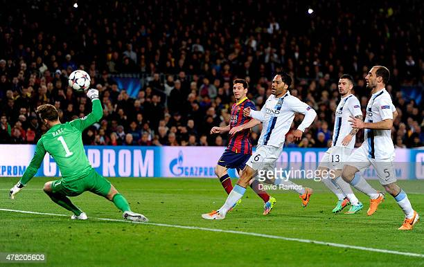 Lionel Messi of Barcelona flicks the ball past goalkeeper Joe Hart of Manchester City to score the opening goal during the UEFA Champions League...