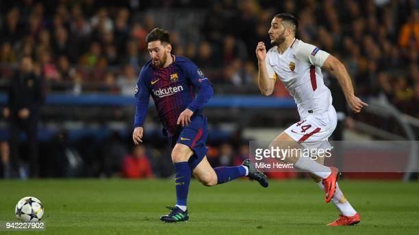 Lionel Messi of Barcelona gets away from Konstantinos Manolas of Roma during the UEFA Champions League Quarter Final Leg One between FC Barcelona and...