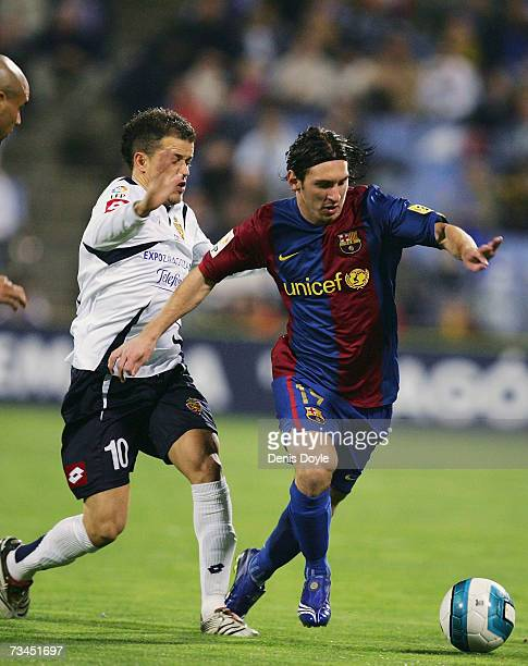 Lionel Messi of Barcelona gets past Andres D'Alessandro of Real Zaragoza during the Kings Cup quarter-final 2nd leg match between Real Zaragoza and...