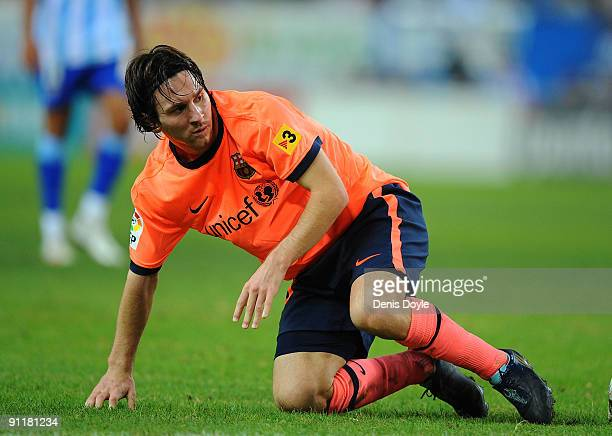 Lionel Messi of Barcelona gets up after taking a knock during the La Liga match between Malaga and Barcelona at La Rosaleda Stadium on September 26,...