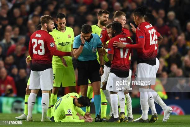 Lionel Messi of Barcelona goes down injured during the UEFA Champions League Quarter Final first leg match between Manchester United and FC Barcelona...