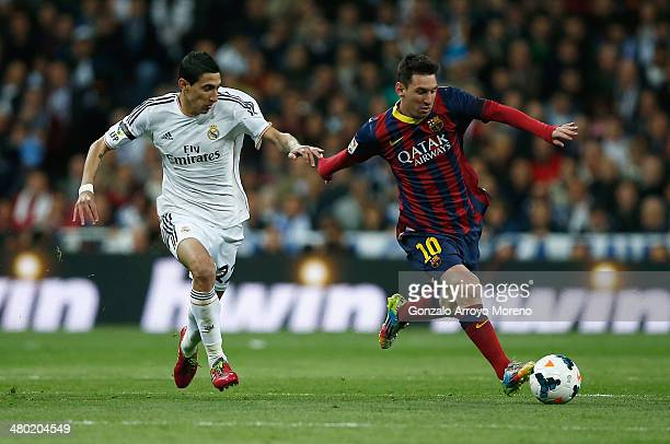 Lionel Messi of Barcelona goes past Angel Di Maria of Real Madrid during the La Liga match between Real Madrid CF and FC Barcelona at the Bernabeu on...