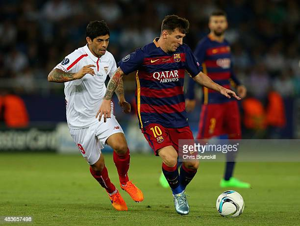 Lionel Messi of Barcelona holds off a challenge from Ever Banega of Sevilla during the UEFA Super Cup between Barcelona and Sevilla FC at Dinamo...
