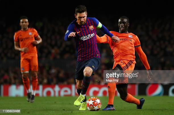 Lionel Messi of Barcelona holds off Ferland Mendy of Olympique Lyonnais during the UEFA Champions League Round of 16 Second Leg match between FC...