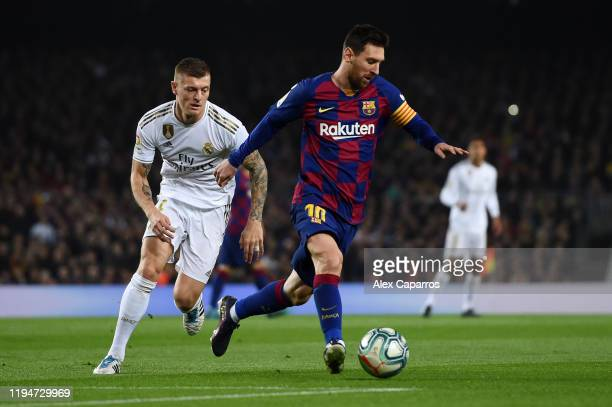 Lionel Messi of Barcelona holds off Toni Kroos of Real Madrid during the Liga match between FC Barcelona and Real Madrid CF at Camp Nou on December...
