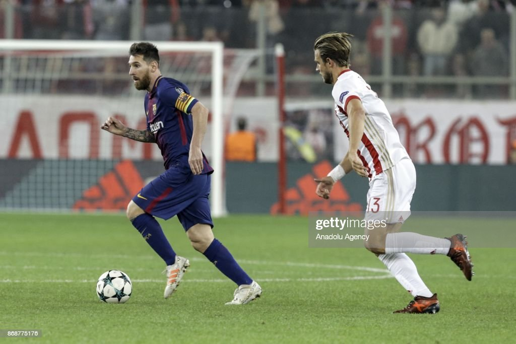 Lionel Messi (L) of Barcelona in action against Guillaume Gillet of Olympiakos during a UEFA Champions League match between Olympiakos and Barcelona at the Giorgos Karaiskakis stadium in Piraeus near Athens, Greece on October 31, 2017.