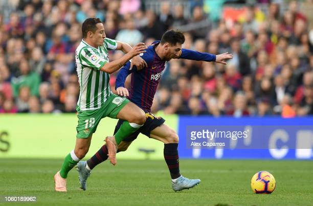 Lionel Messi of Barcelona is challenged by Andres Guardado of Real Betis during the La Liga match between FC Barcelona and Real Betis Balompie at...